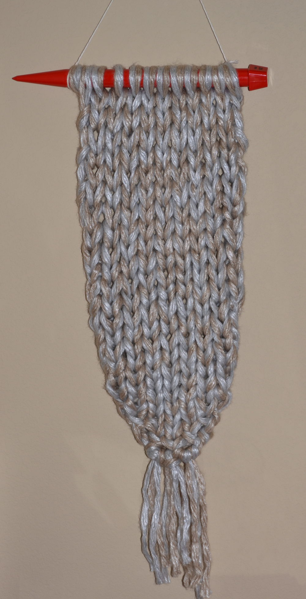 knit wall hanging on knitting needle